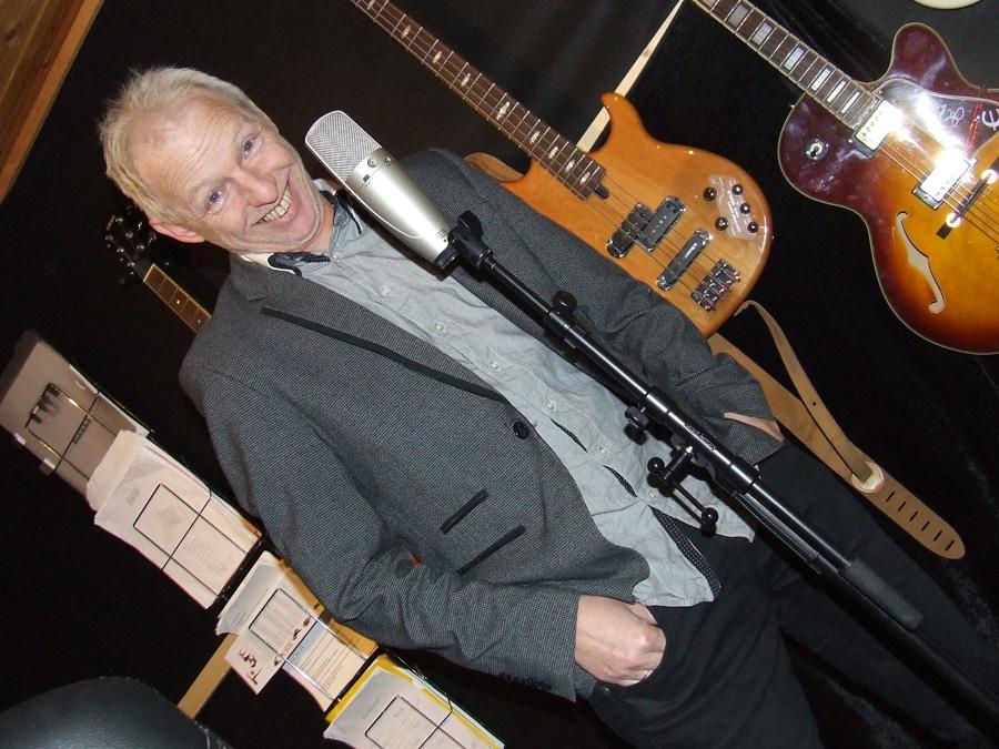 Tom Weum i et av flere nøtteskall. Her med både mikrofon og gitarer. Humor og lyd, med andre ord.